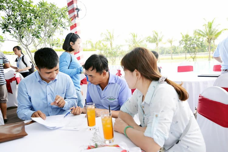 Một nhóm người mua bất động sản ngồi nghe tư vấn dự án.