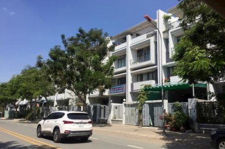 Dãy nhà phố liên kế trong một khu đô thị nằm cạnh đường lớn, ô tô màu trắng, hàng cây xanh.